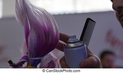 the Barber makes a fashionable hairstyle and styling. Female hairdresser drying her male customer's hair in salon. Model with trendy hairstyle and Hair painting and drying