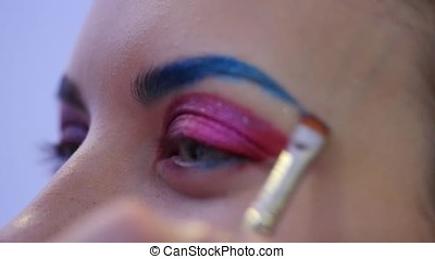 Professional makeup artist working with beautiful young woman. The model does makeup where she painted her lips, eyes and face. Fashionable makeup. A model prepares for fashion show