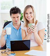 young couple drinking coffee and working together on the laptop in the living-room