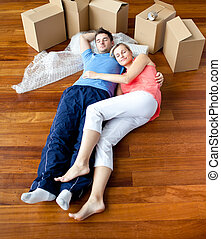 Couple lying on floor by close boxes in new home smiling