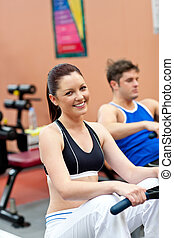 beautiful woman using a rower with her boyfriend in a...