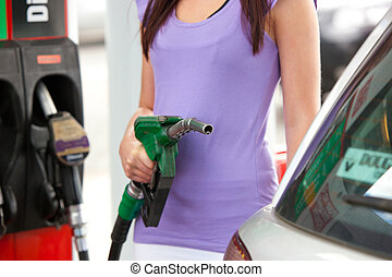 Close-up of a woman refueling car