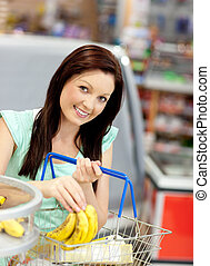 Healthy woman buying bananas