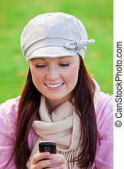 Cute woman on the grass using mobile to write a message