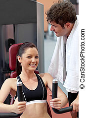 smiling woman sitting on a bench press with her boyfriend standing next her in a fitness centre