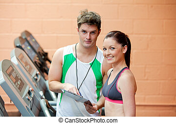 pretty woman on a treadmill with her coach showing results