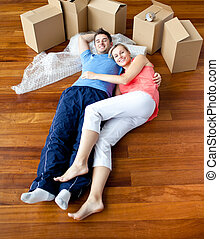 Young couple lying on floor by close boxes in new home...