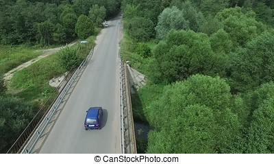Aerial survey of the car rides on the serpentine. Flying over red cabriolet drive the street.Aerial view of red car which goes over the bridge. Traffic on the bridge. Red car.