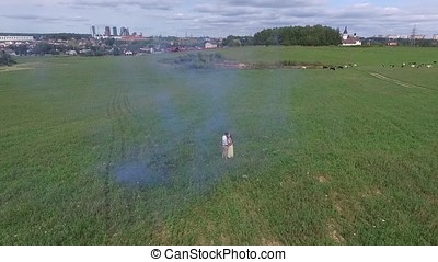 Aerial survey of couple walk on the field with colored smoke in hands. Flying over man and woman run through the field using colored smoke.Lovers running through the field with red and pink smoke bombs or colored smoke on the background of clouds