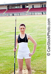 confident athletic woman ready to throw a javelin standing in a stadium looking at the camera