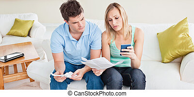 concentrated young couple calculating bills sitting on the sofa in the living-room