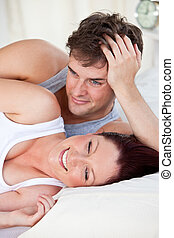 portrait of a laughing pregnant woman lying on the bed with...