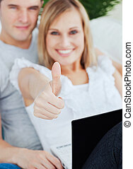young couple working on a laptop with girlfriend doing a thumbs-up sitting in the living-room