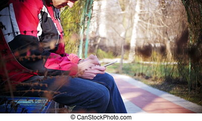 Young Man using a Mobile Phone on a Bench in the City Park