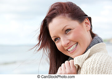 Charming woman feeling the wind standing on the beach