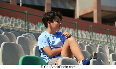 Teenage sport fan supporting his team - Child Boy Sitting In...