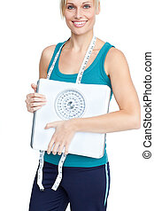Smiling young woman holding a weight scale looking at the...