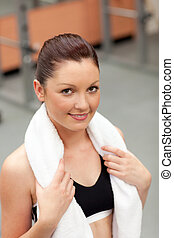 attractive athletic woman with towel around the neck smiling at the camera in a fitness centre