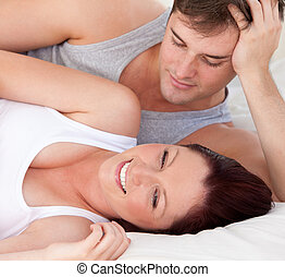 close-up of an affectionate man looking at his pregnant wife lying on the bed at home