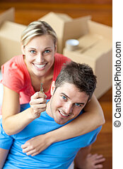 Affectionate couple lying between boxes and holding the key...