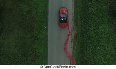 Aerial survey of red cabrioled goes on the road and couple using colored smoke.Flying over classic red convertible car traveling in the countryside at sunset with colored smoke. Lovers in the car drive and use colored smoke.