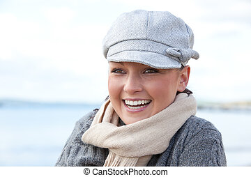 Glad woman on the beach during fall smiling at the camera