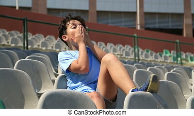 Teenage sport fan supporting his team - Young Boy Sitting On...