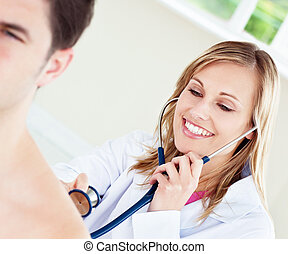 Smiling doctor is examinating her patient in her office