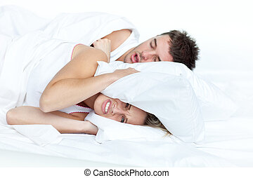 upset woman in bed with her boyfriend snoring putting her...