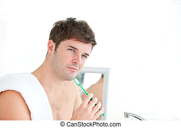 smart young male brushing his tooth with towel on his...