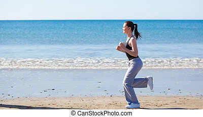 Svelte woman running on the beach with sea in background