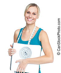 Caucasian young woman holding a weight scale looking at the...
