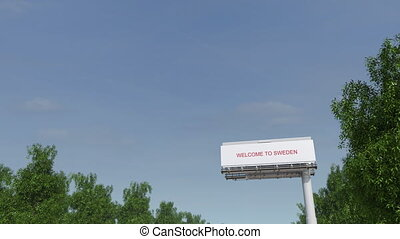 Approaching big highway billboard with Welcome to Sweden...
