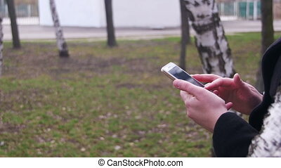 Young Woman using a Smartphone in the City Park. A Girl...