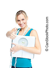 Attractive young woman holding a weight scale looking at the...