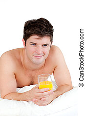 bare-chested man lying on his bed with a glass of orange...