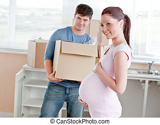 smiling future mother in new kitchen with husband in the...