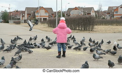 Little child scares pigeons in the park in spring