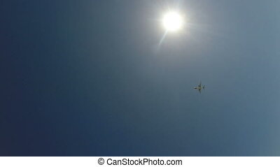 Airplane Flies Overhead - Airplane flies overhead on blue...