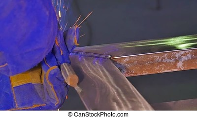 Metal Welding with sparks and smoke. Worker with protective...