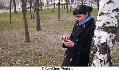 Young Girl using a Mobile Phone in the City Park in the...