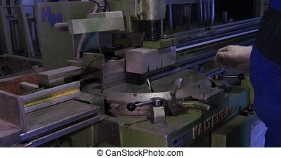 Circular saw for cutting aluminum. Sawing metal. Circular saw cutting metal profile or metal bar. Pressed in the press bar of metal or aluminium circular saw cuts smoothly and flying debris. worker cuts metal on stance. Special equipment for cutting steel. the employee at the bench. Pendular electric saw for metal cutting, Metal sawing close up. Angel grinder make a flash sparks. Industry