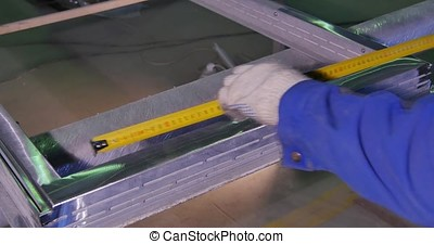 A man measuring a part to make sure of the width before cutting it. a worker measures the frame for the window.Employee working with a protractor to make markings on a metal sheet. Tape measure. Work the sculptor makes drawings layout to the details with a knife. Preparations for the manufacture of products made of granite. Closeup photo of drawing and carpenter's hands who is going to make design. Industry