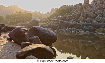 Round Stones Reflect in River Water with Rocky Banks at...