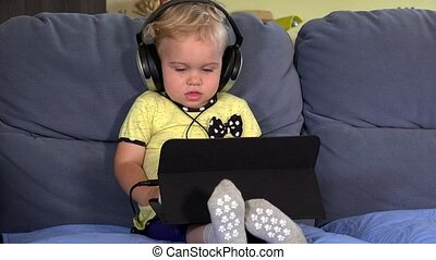 Cute toddler girl with headphones using tablet and listening to music