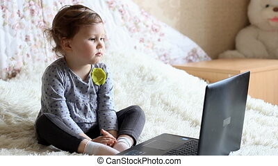 Beautiful girl is sitting at the laptop and is studying the internet.