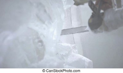 View of sculptor carving ice. Movement. Cut ice with a...