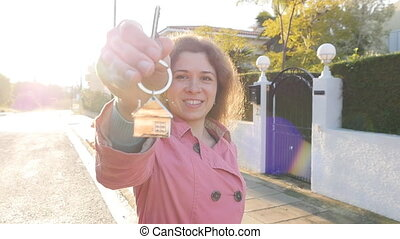 Woman holding house key - Female hand holding house key