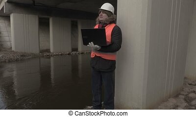 Engineer with laptop under the bridge