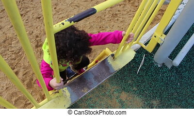 Cute girl climb on playground - Shot of Cute girl climb on...